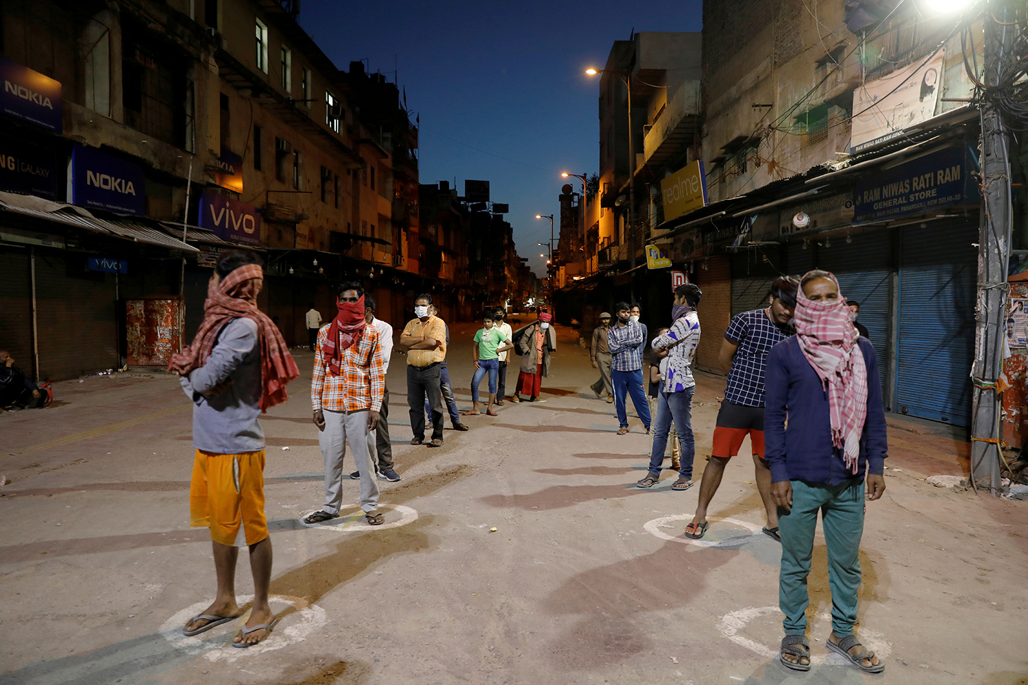 People stand apart in a line to receive free food being distributed on a street during a 21-day nationwide lockdown to limit the spreading of coronavirus disease (COVID-19), in New Delhi